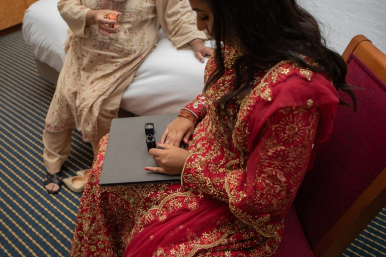 bride painting her nails red with channel nail varnish.