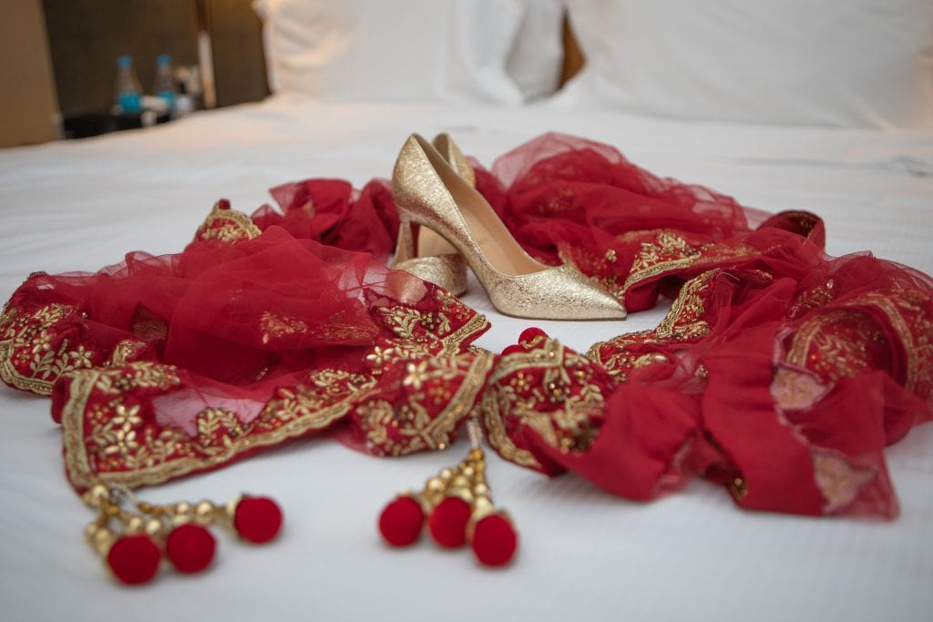 a pair of louboutins surrounded by bright red asian sari